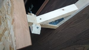Den Winkel verstärken wir mit dem vorher zurechtgesägten Holzkeil. Die im Bild zu sehende Seitenstücke sind im finalen Design nicht mehr nötig. Also, weglassen!